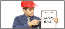 man wearing hardhat holding a 'safety first' sign